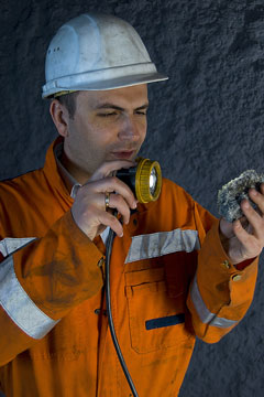 a mining engineer inspecting a mine rock